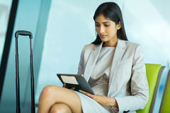 Businesswoman reading emails. Gorgeous young businesswoman at airport reading her emails on tablet computer royalty free stock photos