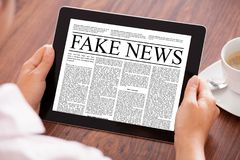 Businesswoman Reading Fake News On Digital Tablet At Table. Cropped image of businesswoman reading fake news on digital tablet at table in office royalty free stock images