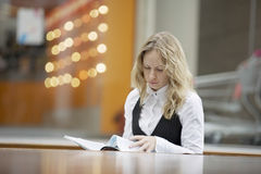 Businesswoman Reading Magazine At Foodcourt Stock Images