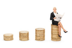 Businesswoman reading the news seated on coins Stock Photos