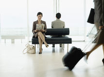 Businesswoman Reading Newspaper At Airport Lobby. Businesswoman sitting on bench and reading newspaper in airport Royalty Free Stock Photography