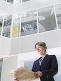 Businesswoman reading newspaper in atrium of office building low angle view. Low angle view of a businesswoman reading newspaper in atrium of office building Royalty Free Stock Photo