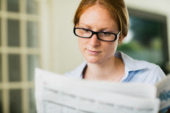 Businesswoman Reading a Newspaper at Home Stock Photography