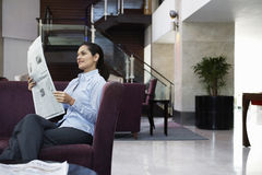 Businesswoman Reading Newspaper In Hotel Lobby Royalty Free Stock Photography