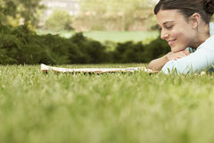 Businesswoman Reading Newspaper While Lying On Grass Royalty Free Stock Photo