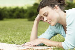 Businesswoman Reading Newspaper While Lying On Grass At Park Royalty Free Stock Images