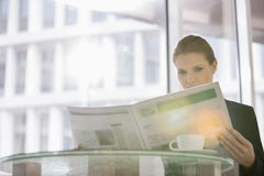 Businesswoman reading newspaper at office cafe Stock Photos