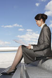 Businesswoman Reading Newspaper Outdoors Royalty Free Stock Image