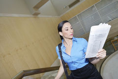 Businesswoman Reading Newspaper On Staircase Royalty Free Stock Photography
