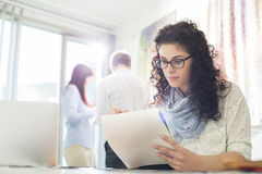 Businesswoman reading notepad at creative office with colleagues in background Royalty Free Stock Images