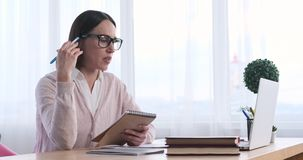 Businesswoman reading notes and discussing on video conference using laptop