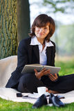 Businesswoman reading outdoor in park Royalty Free Stock Images