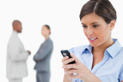 Businesswoman reading text message with associates Stock Images