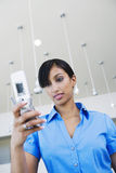 Businesswoman Reading Text Message On Cell Phone Royalty Free Stock Image