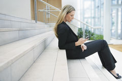 Businesswoman Reading Text Message On Office Steps Stock Image