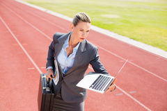 Businesswoman ready to run with a laptop and briefcase Stock Photography