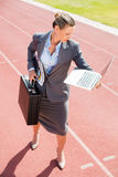 Businesswoman ready to run with a laptop and briefcase. On running track Royalty Free Stock Photography