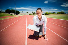 Businesswoman ready to run with a laptop. Businesswoman ready to run on running track with a laptop Stock Image