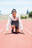 Businesswoman in ready to run position. On running track Stock Images