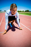 Businesswoman ready to run on running track Royalty Free Stock Photography