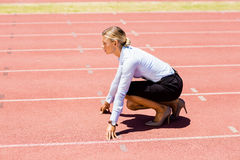 Businesswoman ready to run on running track. On a sunny day Stock Image