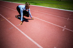 Businesswoman ready to run on running track Royalty Free Stock Photo
