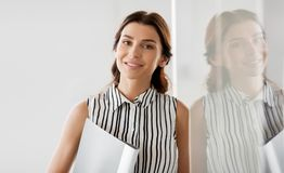 Businesswoman or realtor with folder at office. Business, people and corporate concept - businesswoman or realtor with folder at office glass wall Royalty Free Stock Photo