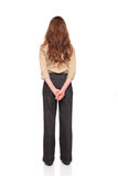 Businesswoman - rear view hands clasped. Isolated full length studio shot of the rear view of a Caucasian businesswoman standing with hands clasped behind her Stock Image