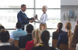 Businesswoman receiving award from businessman in a business seminar. Front view of mixed race businesswoman receiving award from mixed race businessman in front royalty free stock photo