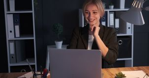 Businesswoman receiving good news on laptop. Excited businesswoman receiving good news on laptop during night shift at office stock footage
