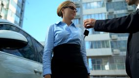 Businesswoman receiving keys to luxury auto from dealer, car loan or purchase. Stock photo royalty free stock photos