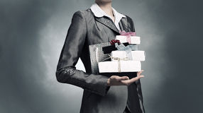 Businesswoman receiving or presenting gifts . Mixed media Stock Photo