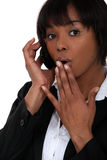 Businesswoman receiving shocking news. Over the phone Royalty Free Stock Image