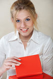 Businesswoman with red box. Young beautiful businesswoman with blond hair and blue eyes in white shirt opening a red box Royalty Free Stock Photography