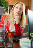 Businesswoman in red having a tedious time. Blonde businesswoman in red having a tedious time at office Stock Photo