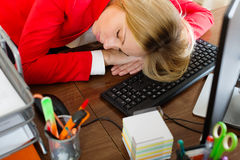 Businesswoman in red sleeping at office desk Stock Photography
