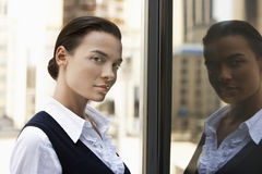 Businesswoman With Reflection In Window Stock Photos
