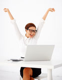 Businesswoman rejoicing. Beautiful young businesswoman sitting at a table with her laptop rejoicing and extending her arms into the air laughing with joy on a royalty free stock photos