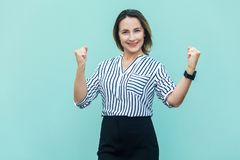 Businesswoman rejoicing for his success.  on light blue. Background. Indoor, studio shot Royalty Free Stock Photography