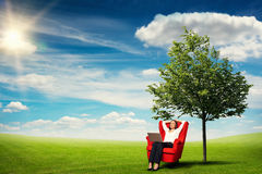 Businesswoman relasing at outdoor. Smiley businesswoman with laptop on knees relaxing on the red chair over beautiful landscape with green meadow, tree and blue Royalty Free Stock Photography