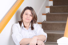 Businesswoman relaxed sitting on stairs at home. Royalty Free Stock Image