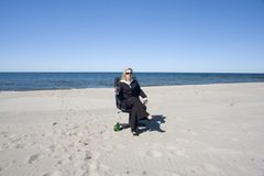 Businesswoman relaxes on beach stock photography