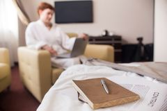 Businesswoman Relaxing in Hotel during Trip. Blurred portrait of unrecognizable businesswoman wearing bathrobe working with laptop in hotel room, focus on Stock Images