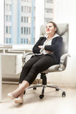 Businesswoman relaxing in leather chair at office Stock Photos