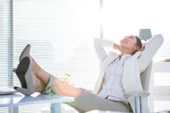 Businesswoman relaxing with legs on desk Royalty Free Stock Images