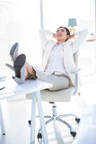 Businesswoman relaxing with legs on desk Stock Photos