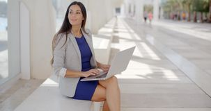 Businesswoman relaxing and working on a laptop stock footage