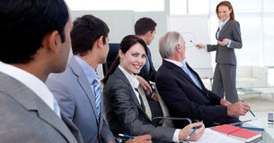 Businesswoman reporting sales figures to her team Stock Photography