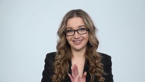 Businesswoman is reporting and tells a lot of interesting informations against grey background, slow motion. Businesswoman is reporting and tells a lot of stock video footage