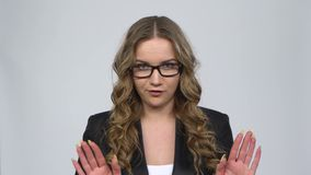 Businesswoman is reporting and tells a lot of interesting news against grey background. At studio. Girl with wavy hair and glasses wearing a black business suit stock video footage